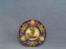 italian ceramic plate hand painted with blue background and rural landscape in the center