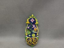 Hand painted holy water stoup with floral decorations on a blue background.
