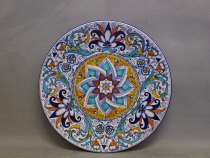 Hand painted majolica plate in Persian Palmette style with geometric flower in the center