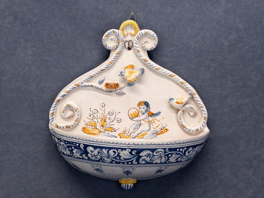 Holy water stoup painted with decoration in soft colors and spring scene with putto